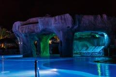 游泳池和洞穴迷人的舒适夜视图  免版税库存照片