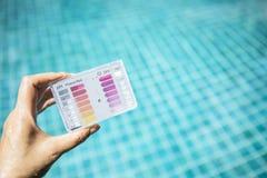 游泳池水质测试在女孩的测试成套工具移交被弄脏的蓝色游泳池水背景 库存照片