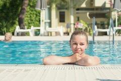 游泳池的一名年轻可爱的白肤金发的妇女 库存图片