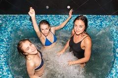 游泳池的三个女性朋友 免版税库存图片