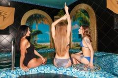 游泳池的三个女性朋友 免版税库存照片
