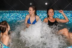 游泳池的三个女性朋友 免版税图库摄影