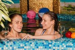 游泳池的两个女性朋友 库存图片