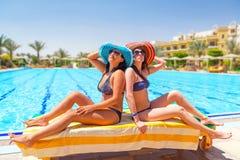 游泳池的两个被晒黑的女孩 免版税库存图片