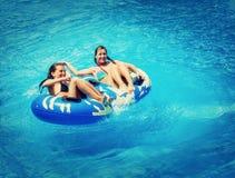 游泳池的两名妇女 免版税库存照片