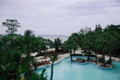游泳池的在海,在庭院旁边的太阳懒人装饰海岛 库存图片