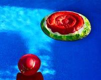 游泳池的妇女和西瓜漂浮 图库摄影
