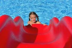 游泳池的小女孩与幻灯片 库存照片