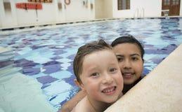 游泳池的微笑的孩子在晴朗 库存图片