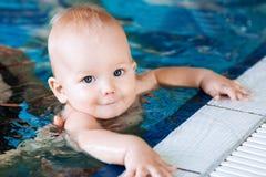 游泳池的微笑的迷人的婴孩 免版税库存照片