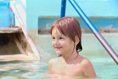 游泳池的愉快的微笑的小女孩 免版税库存照片