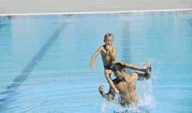 游泳池的愉快的父亲和儿子 免版税库存照片