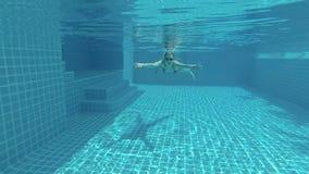 游泳池的愉快的美丽的可爱的少妇,水下的看法 行动照相机 影视素材