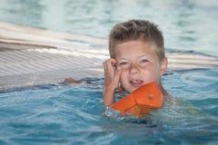 游泳池的男孩与可膨胀的臂章 免版税库存图片