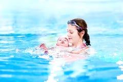 游泳池的逗人喜爱的矮小的婴孩与他的母亲 免版税库存照片