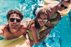 游泳池的年轻朋友 免版税图库摄影