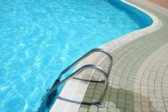 游泳池被塑造的水梯子 免版税库存图片
