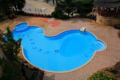 游泳池视图,在庭院旁边的太阳从上面懒人和塔 库存照片