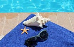 游泳池边假日风景壳毛巾太阳镜 库存照片