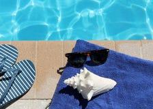 游泳池边假日风景壳毛巾皮带太阳镜 免版税库存照片