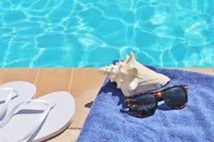 游泳池边假日风景壳毛巾皮带太阳镜 库存照片