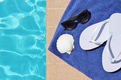 游泳池边假日风景壳毛巾皮带太阳镜 免版税库存图片