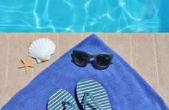 游泳池边假日风景壳毛巾皮带太阳镜 库存图片