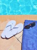 游泳池边假日风景毛巾皮带太阳镜 免版税库存图片