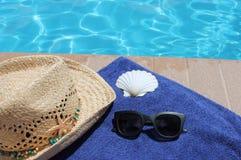游泳池边假日风景游泳池边假日风景毛巾、牛仔帽、壳和太阳镜 免版税库存照片