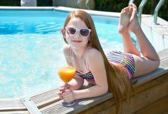 游泳池边的一个微笑的小女孩 免版税图库摄影
