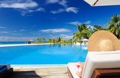 游泳池边的妇女有世界性鸡尾酒的 免版税图库摄影