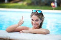 游泳池边缘的性感的妇女  免版税库存图片