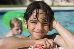 游泳池边缘的男孩  免版税库存图片