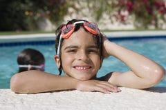 游泳池边缘的男孩  库存图片
