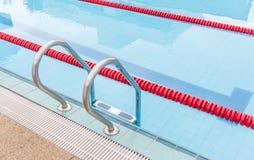 游泳池金属梯子看法与明显的车道的 图库摄影