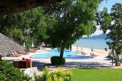 游泳池,在庭院旁边的太阳懒人在海附近 库存照片