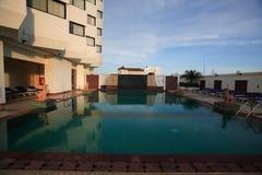游泳池,太阳懒人在大厦的城市 免版税图库摄影