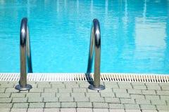游泳池水梯子前面 免版税库存图片