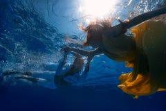 游泳的夫妇在水面下 图库摄影