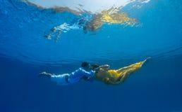 游泳的夫妇在水面下 免版税库存照片