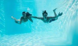 游泳的夫妇握手和在水面下 免版税库存照片