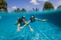 游泳的女孩在水面下 库存照片