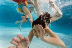 游泳的子项在水面下 免版税库存图片