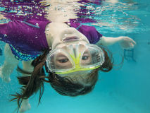 游泳的小女孩在水面下获得乐趣 库存照片