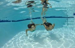 游泳的朋友在水面下 免版税库存照片