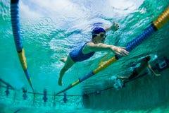 游泳的水下的女孩培训 免版税库存照片