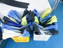 游泳的许多多彩多姿的橡胶飞翅,潜水,体育在篮子,在一条浮动小船,船,在a的巡航划线员的一个箱子在 免版税图库摄影