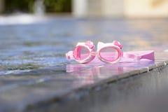 游泳的玻璃在水池旁边被安置 免版税图库摄影