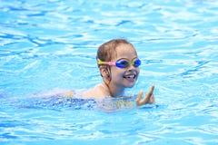 游泳的玻璃的快乐的孩子在水池 免版税图库摄影