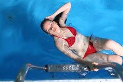 游泳的年轻红色比基尼泳装女性在水池 库存图片